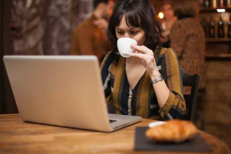 Brunette business woman enjoying a cup of cup while reading an email on the laptop